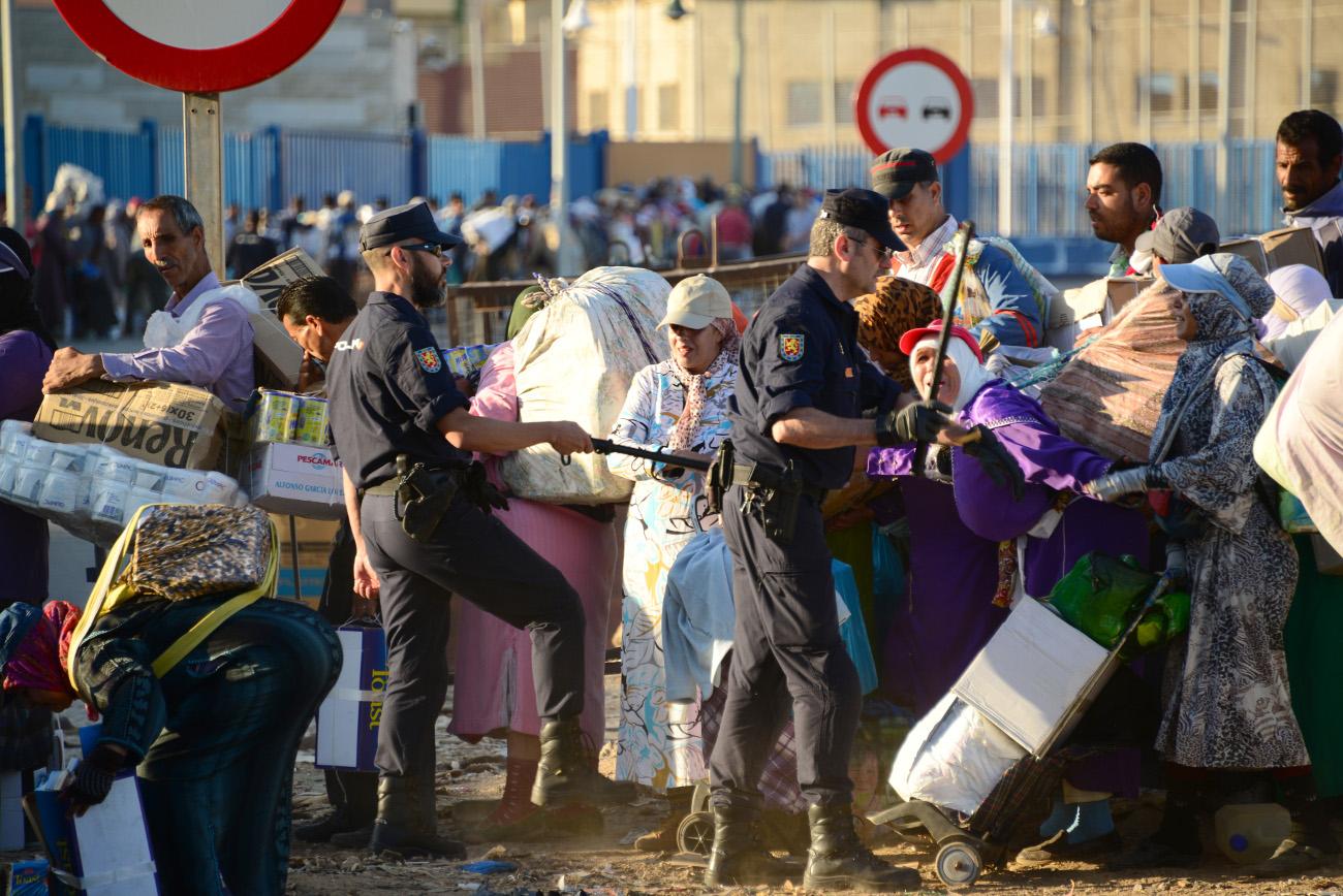 Policiers espagnols malmenant les passeurs de marchandises à Melilla.